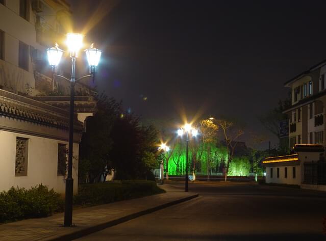 庭院灯是一种室外照明灯具,其高度通常在6米以下,主要部件是由:光源、灯具、灯杆、法兰盘、基础预埋件组成,因具有美化和装饰环境的特点,故也被称之为景观庭院灯。今天我们讨论的是小区庭院灯该如何设置:  1、应用范围 庭院灯为小区主要道路、街道的主要功能性照明灯饰,为夜间行人的安全行走提供了有效的照明保证,灯具高度一般3-5米,有效照明半径8-10米,布置间距在15-20米左右,考虑到灯具与景观的协调性,可以在具体点位布置上安装于乔木侧边,使之不破坏景观的协调性。 2、选型要求 光源选择: 不宜选择白炽灯(寿命